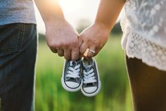 man and woman holding baby converse shoes